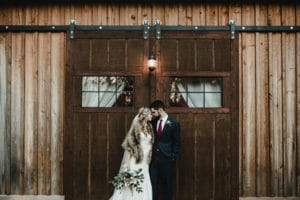 Bride and groom in front of barn at The Wheeler House
