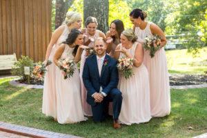 Bridesmaids with groom at barn wedding venue