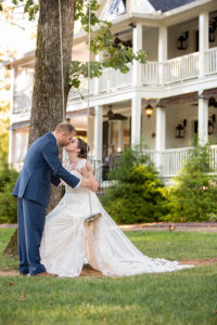 Bride and groom kissing on the swing at The Wheeler House