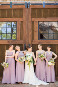 Bridesmaids and bride in front of The Wheeler House Barn
