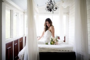 Bride sitting on hanging bed on The Wheeler House Porch